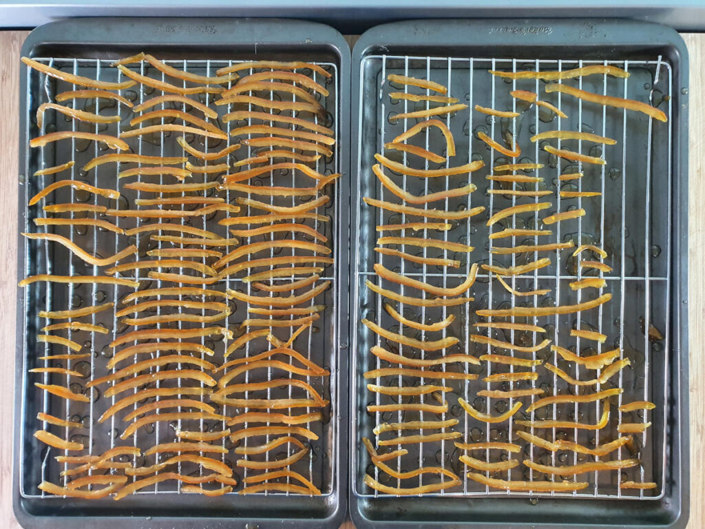 two tray of candied peel laid out on cooling racks on top of baking tray to catch the drips.