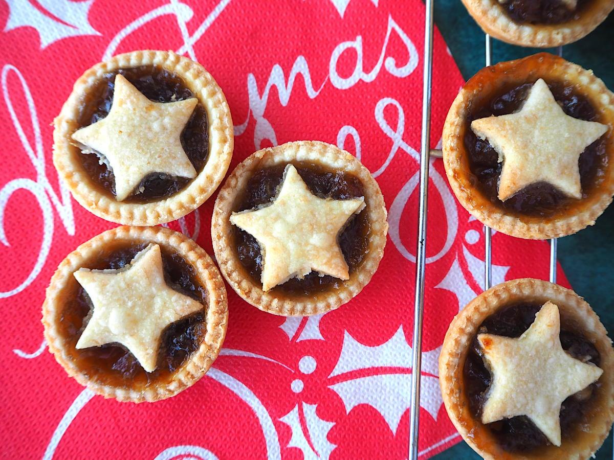 Mincemeat tarts on a Christmas serviette, next to mincemeat tarts on a cooling rack.