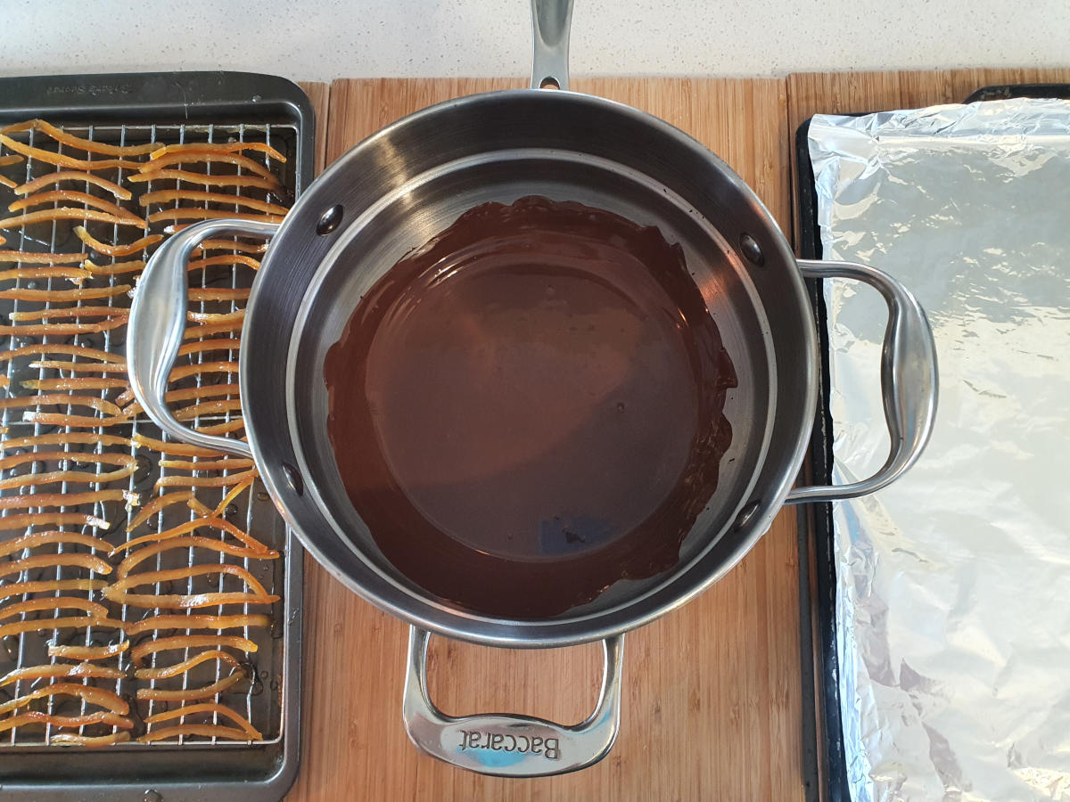 setting up for chocolate covering, tray of dried peel on the left, double boiler with melted chocolate in the middle, tray covered in foil on the right.