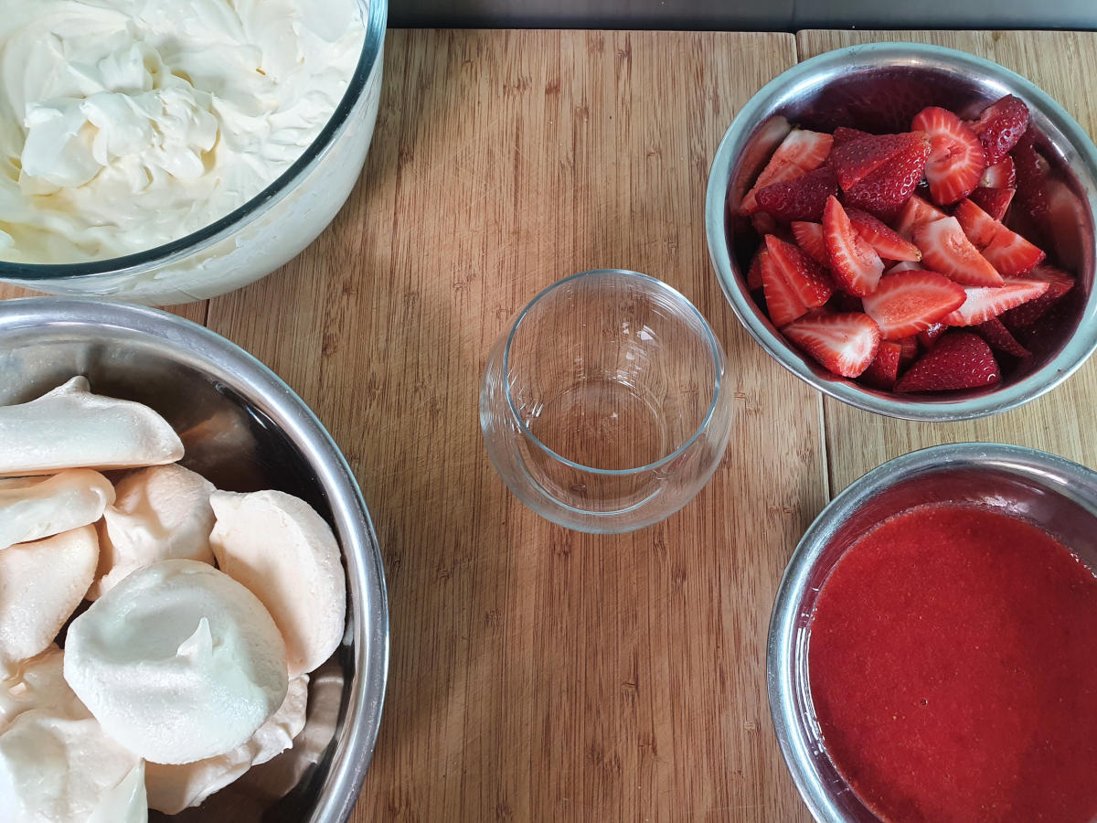 made up ingredients ready to assemble, cream mix, meringues, chopped strawberries and strawberry sauce.