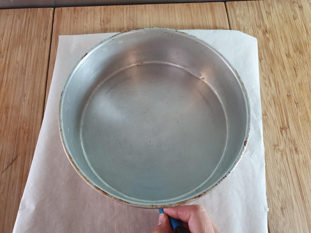 tracing cake tin shape onto baking paper with a pen.