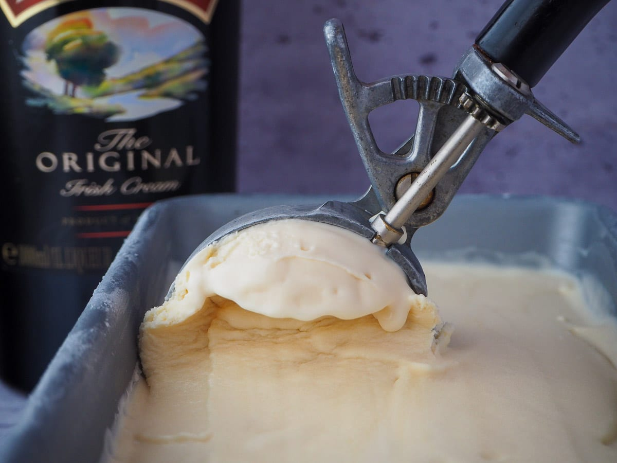 Scooping Baileys ice cream from a pan with a black vintage ice cream scoop and bottle of Baileys in the background.