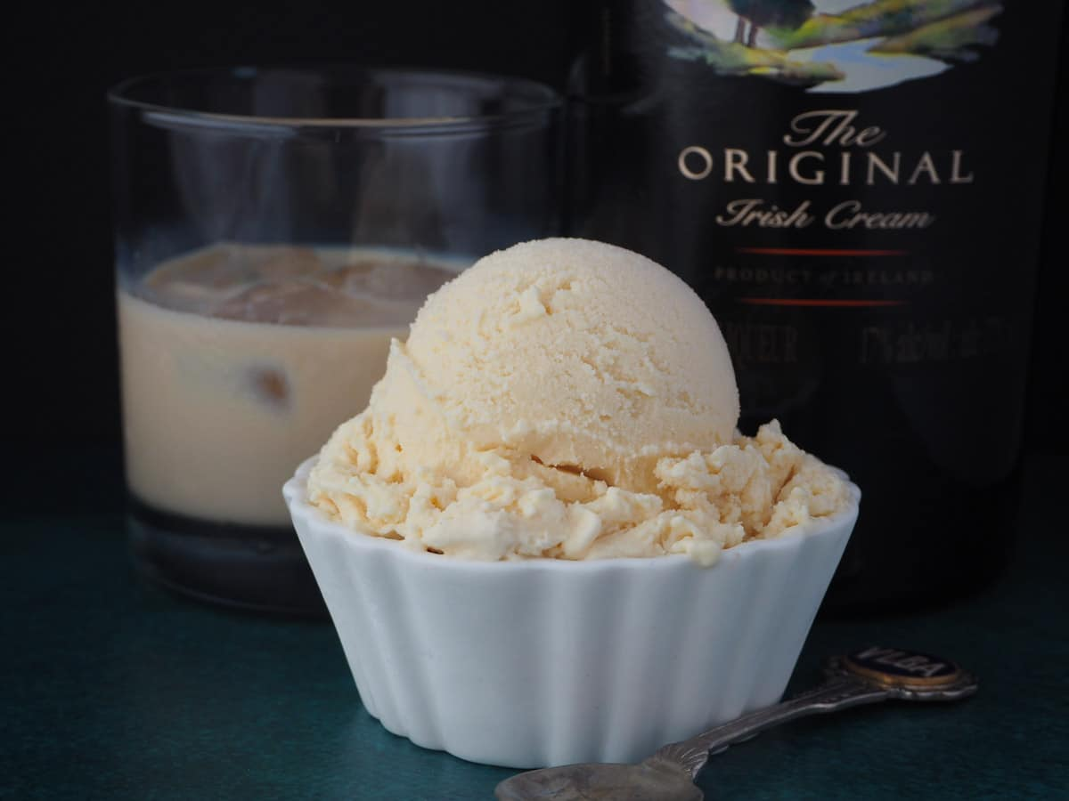 Baileys ice cream scoop with a vintage spoon on the side and glass of Baileys and bottle of Baileys in the background.