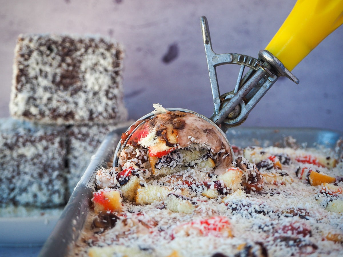 Scooping lamington ice cream from a pan with a vintage ice cream scoop, with lamingtons in the background.