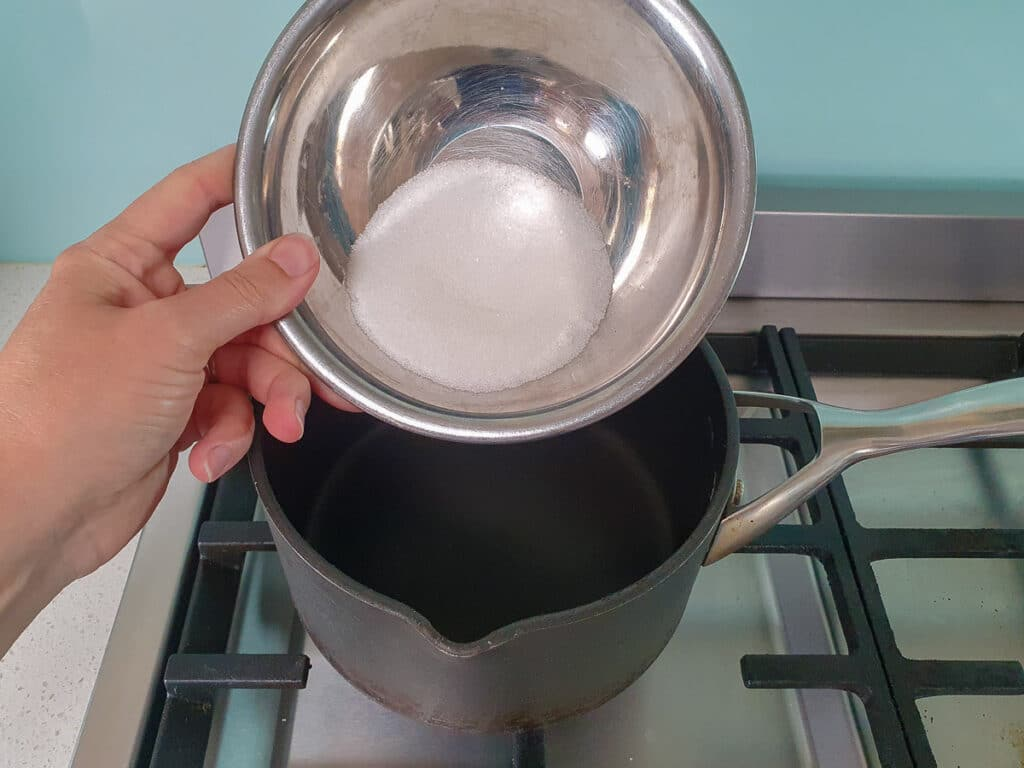 Adding sugar to pot for strawberry sauce.
