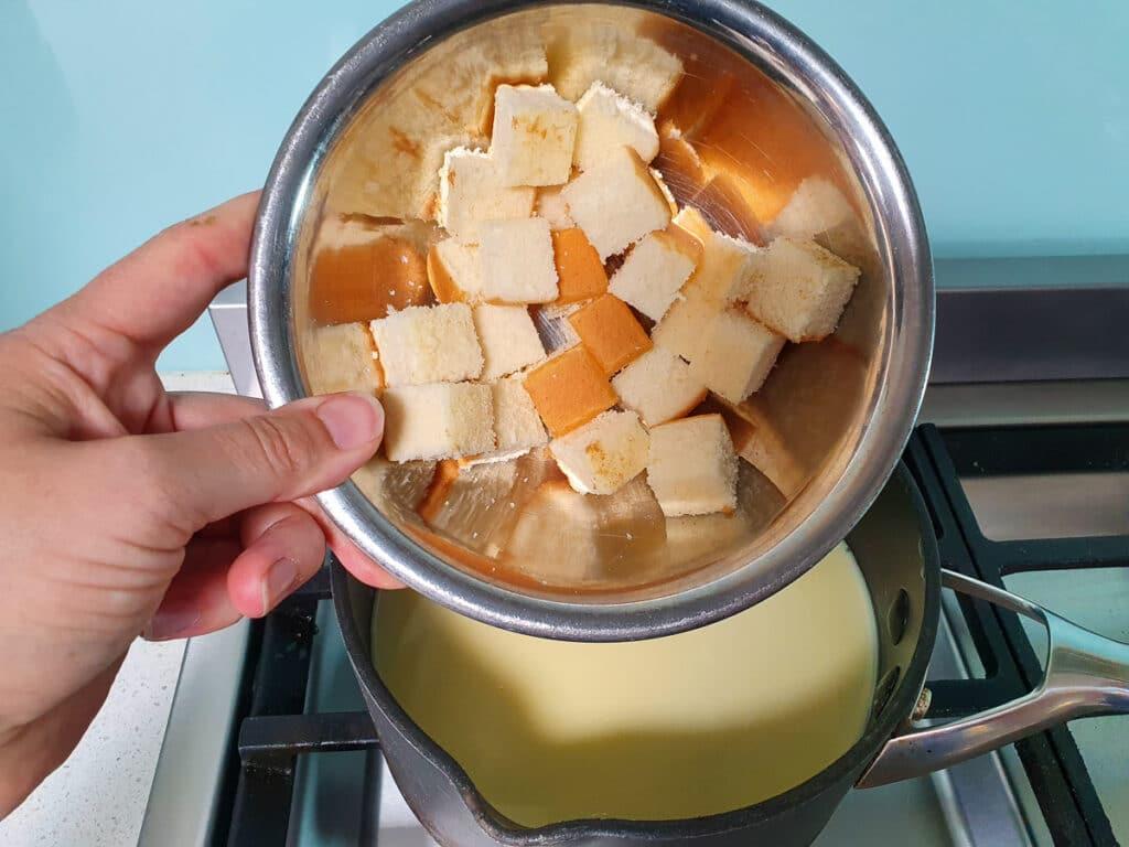 Adding chopped sponge cake to ice cream mix.