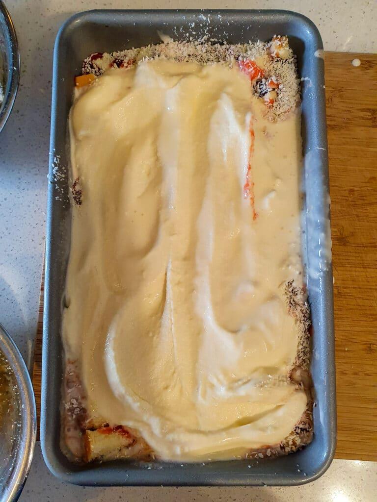 Adding second layer of sponge ice cream to pan.