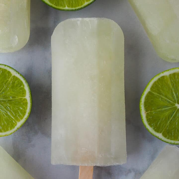 Lime popsicles surrounded by fresh cut limes.