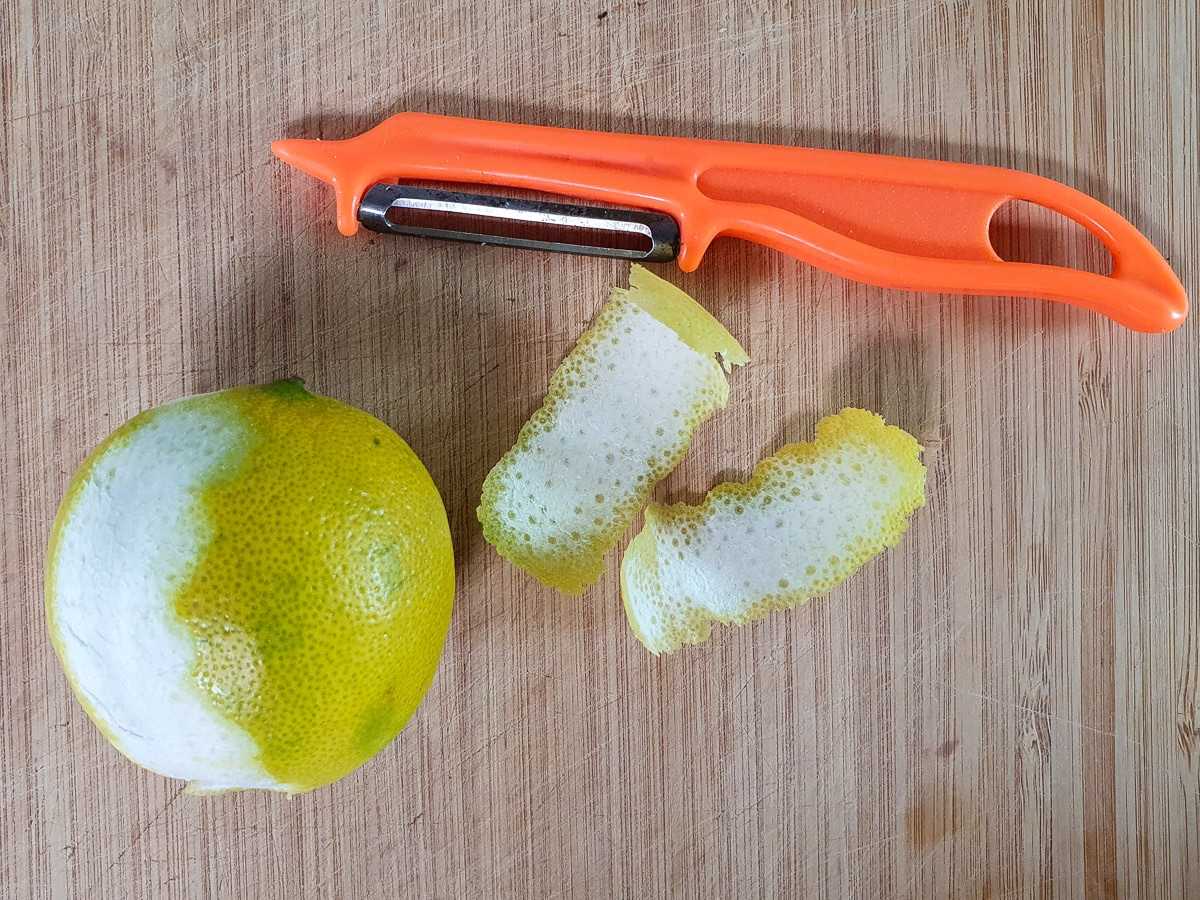Using a peeler to peel zest strips off two limes.