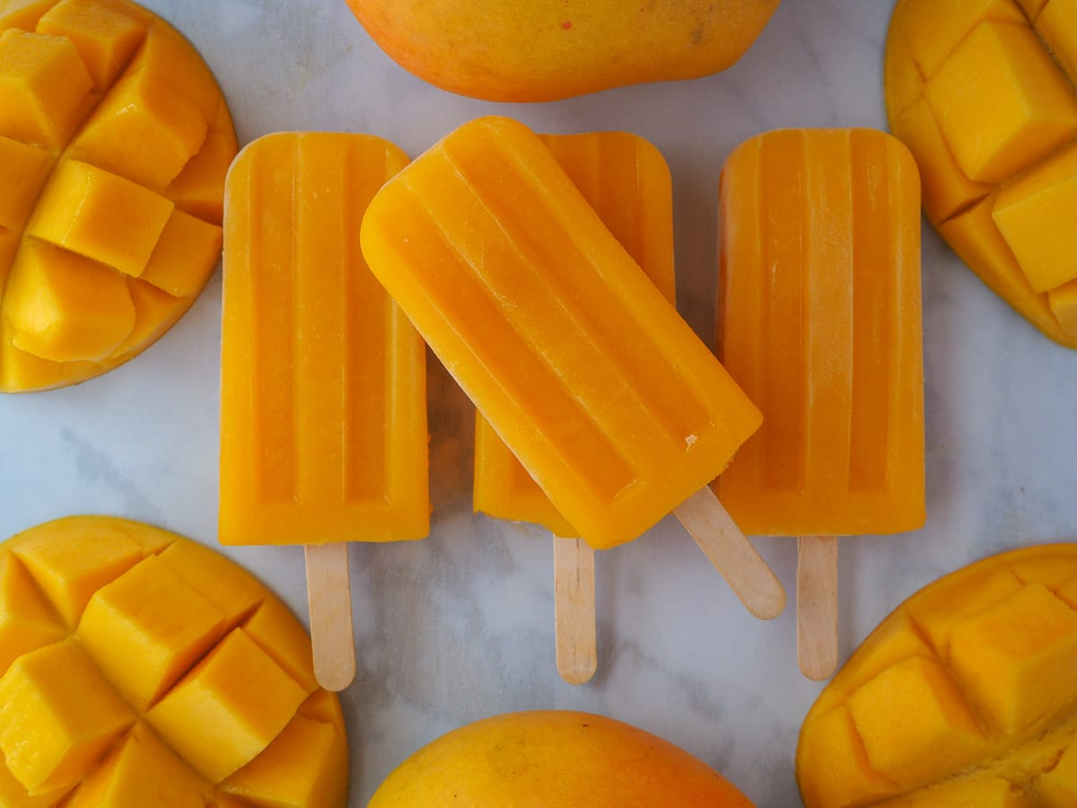 Row of three mango popsicles, with one stacked on top in the middle, surrounded by fresh mangos.