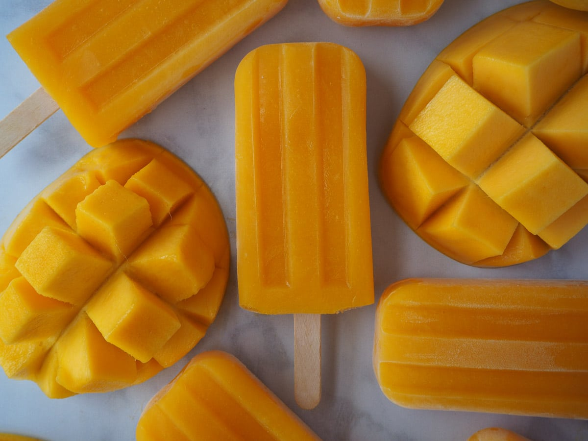 Mango popsicles surrounded by fresh mango pieces.