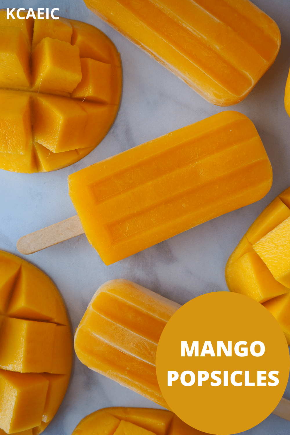 Row of three mango popsicles in a vertical row, surrounded by fresh mango, with text overlay, KCAEIC and mango popsicles.
