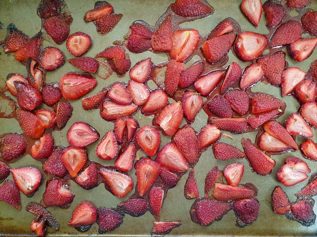 Roasted strawberries showing juices just starting to caramelize around the edges.