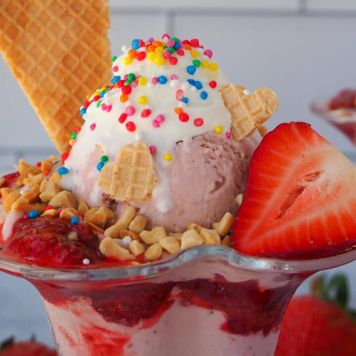 Close up of strawberry sundae with strawberry ice cream, strawberry sauce, fresh strawberry, whipped cream, nuts, waffles and rainbow sprinkles, with a second sundae in the background.