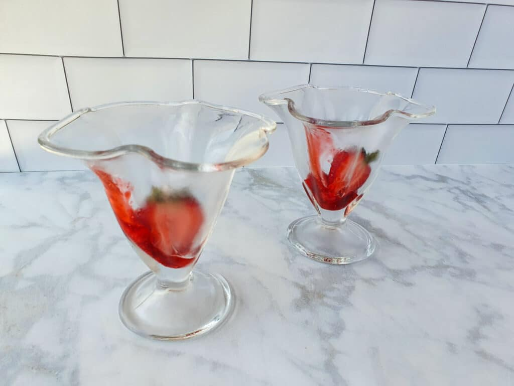 Adding fresh strawberries to the bottom of the sundae glass.