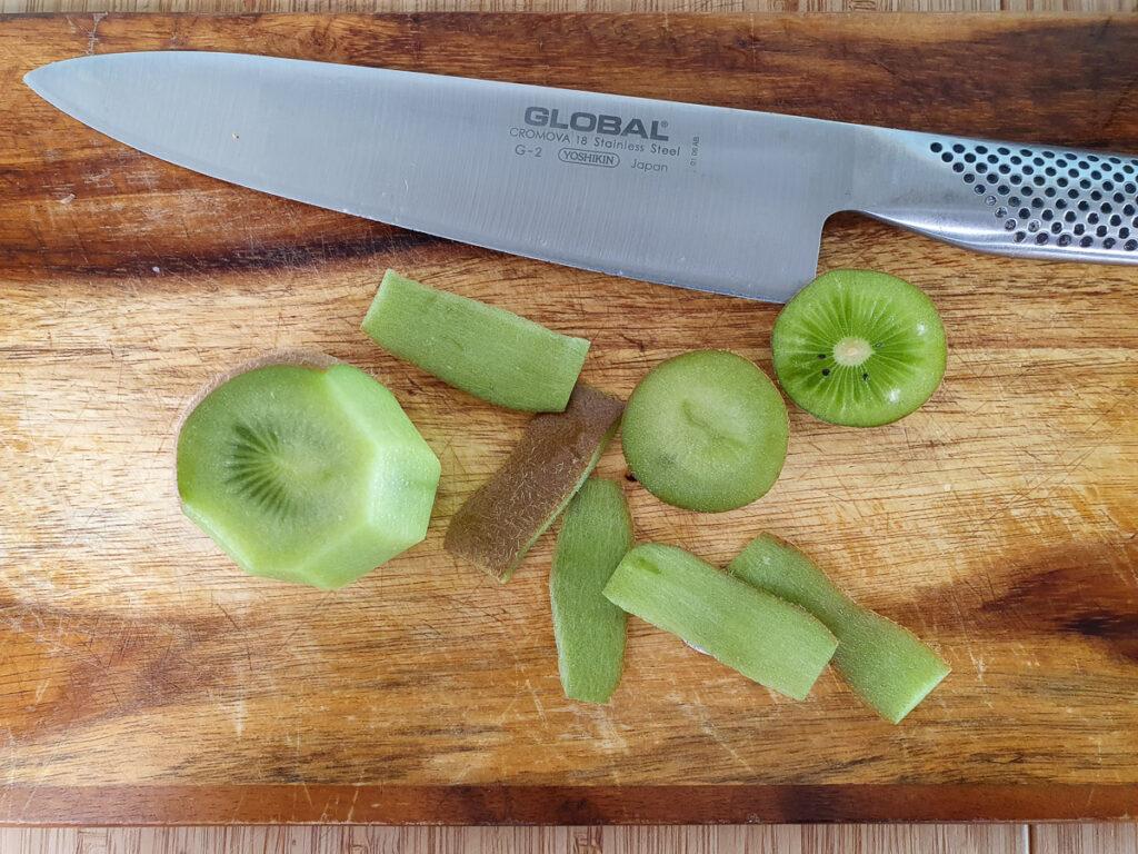 Cutting skins off kiwi fruit and cutting into chunks.