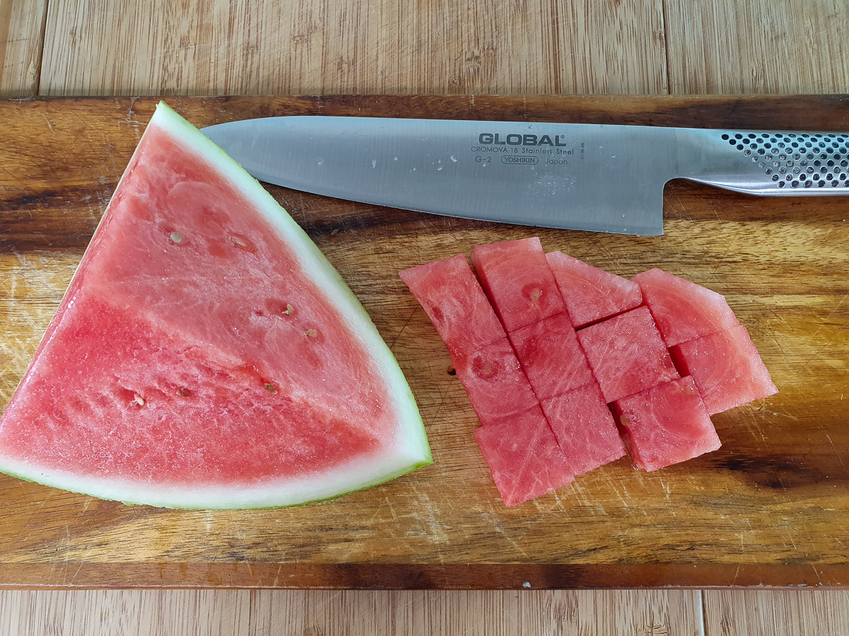 Cutting up watermelon into chunks and cutting off rind.