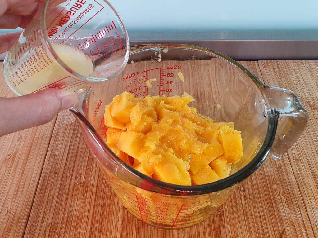 Adding lime juice to mango flesh in jug.