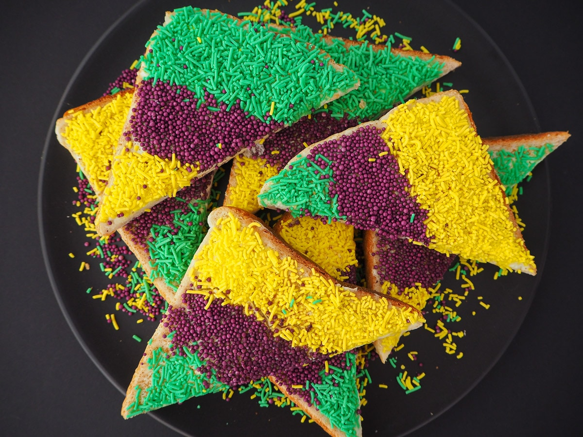 Slices of King cake sprinkles bread on a black plate.