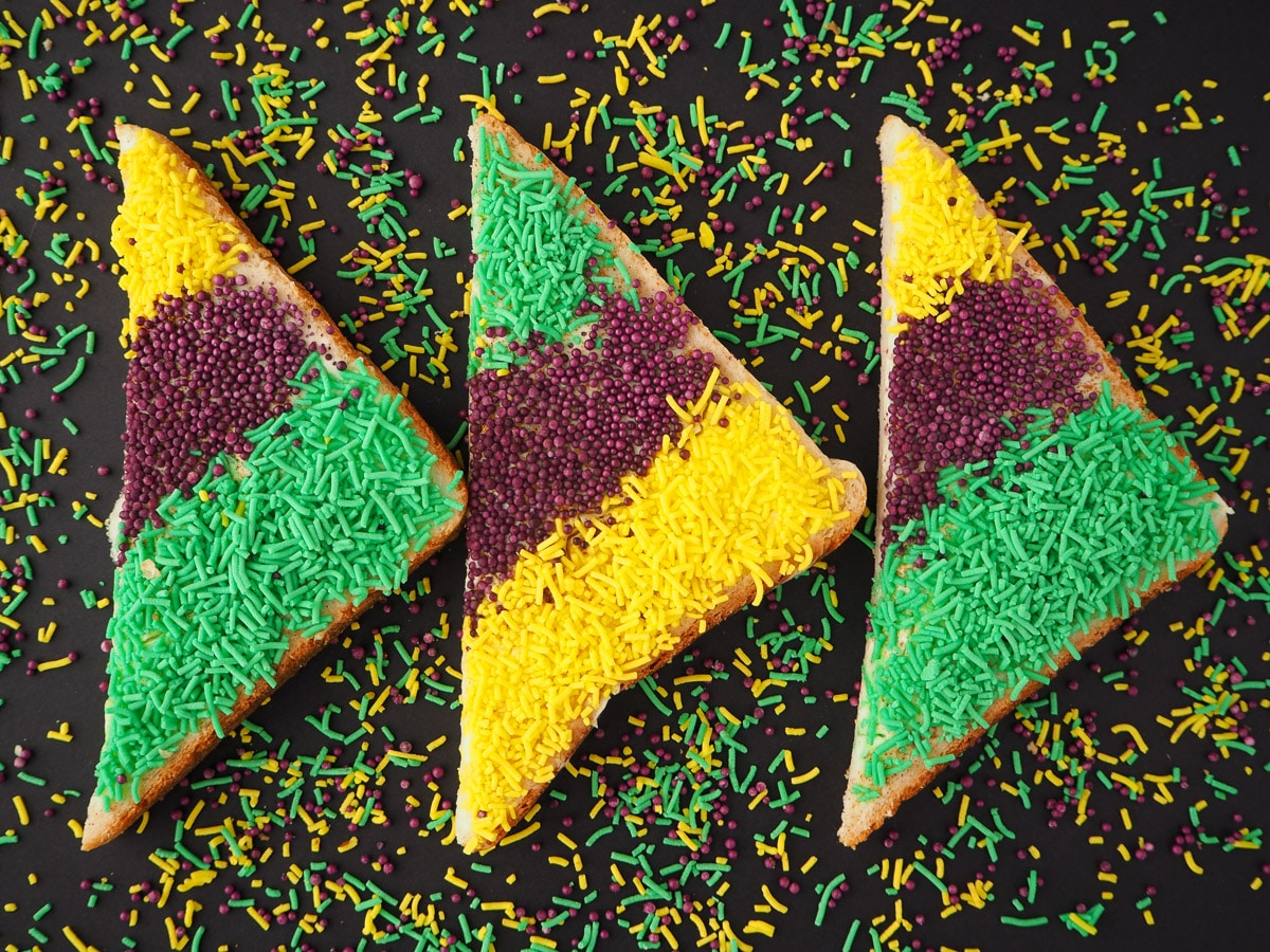Horizontal line of three slices of King cake sprinkles bread, surrounded by sprinkles.