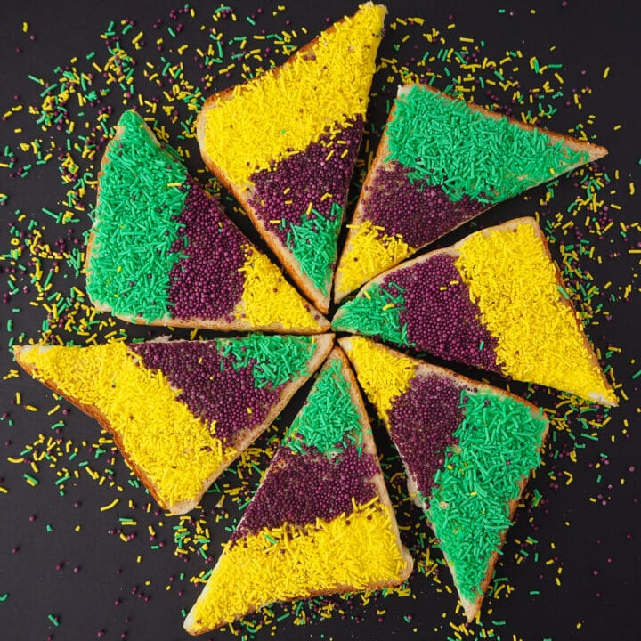 Several slices of triangle cut King cake sprinkles bread, arranged in a star shape.