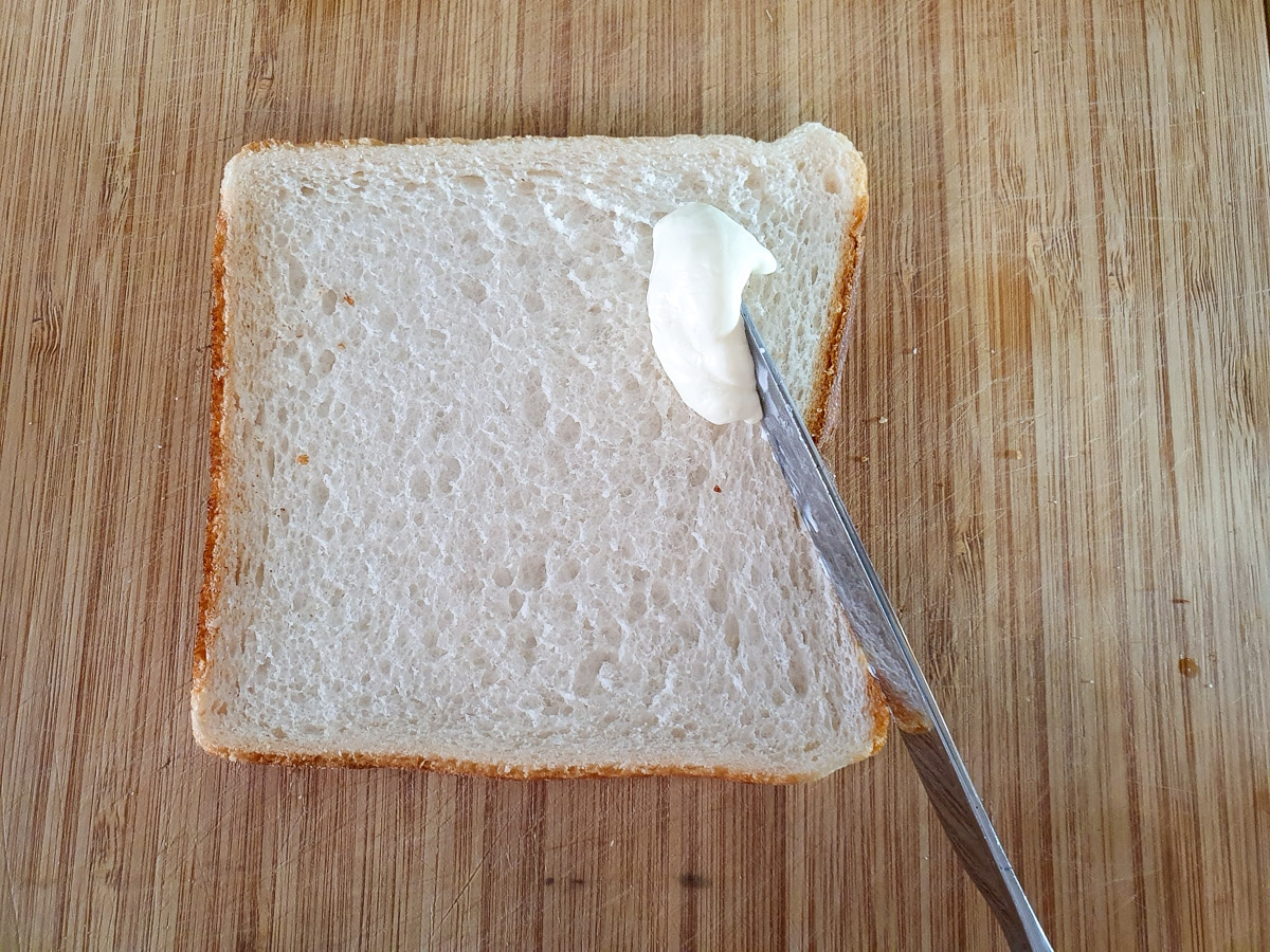 Spreading softened cream cheese over bread.