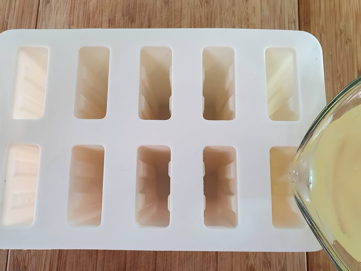 Pouring popsicle mix into popsicle molds.