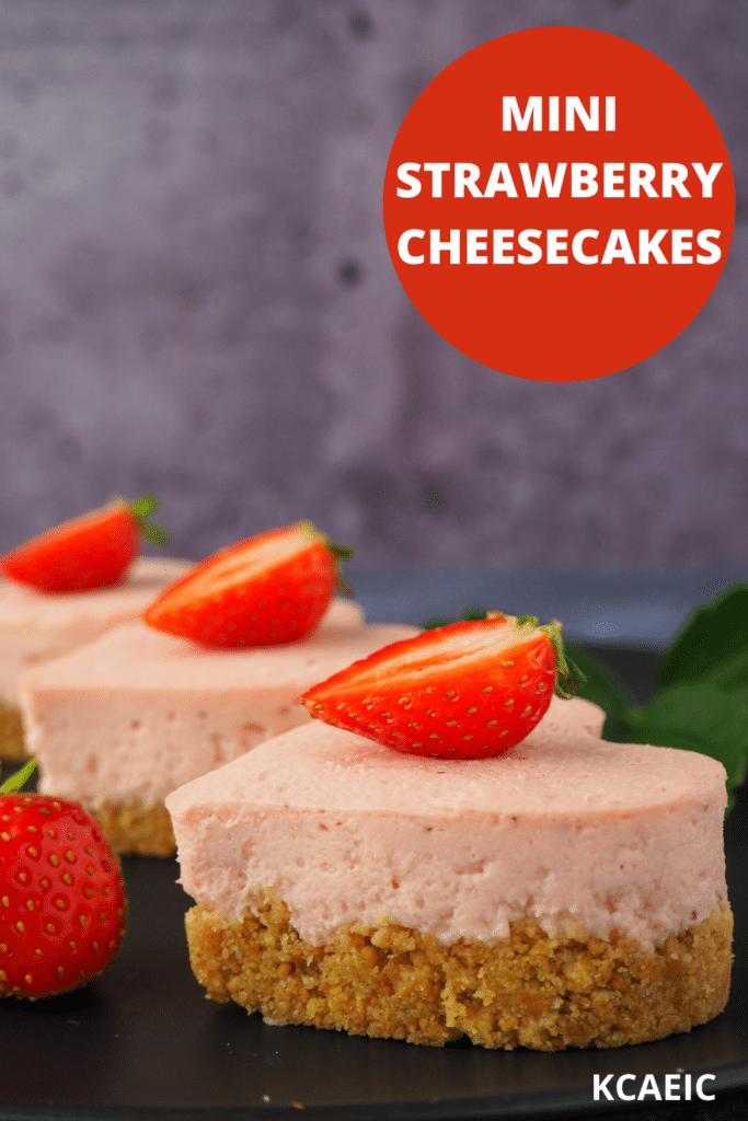 Side view three mini strawberry cheesecakes with fresh strawberries and strawberry leaves and text overlay, mini strawberry cheesecakes and KCAEIC.