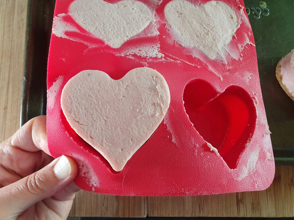Removing heart shaped cheesecake by pulling back from edge and pushing up from the bottom.
