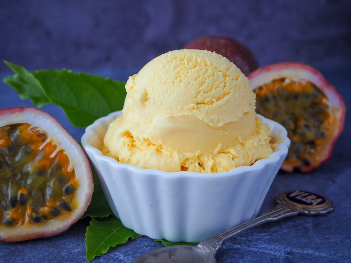 Scoop of passion fruit ice cream with fresh passion fruit and passion fruit leaves and a vintage spoon