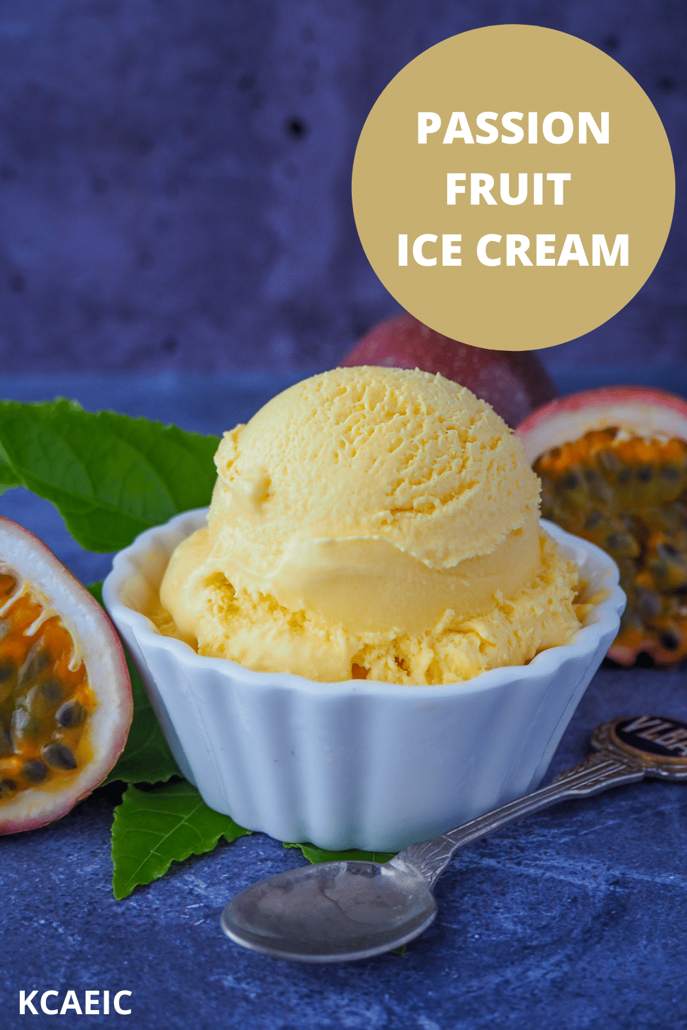 Scoop of passion fruit ice cream with fresh passion fruit and passion fruit leaves and a vintage spoon, with text over lay passion fruit ice cream, KCAEIC.