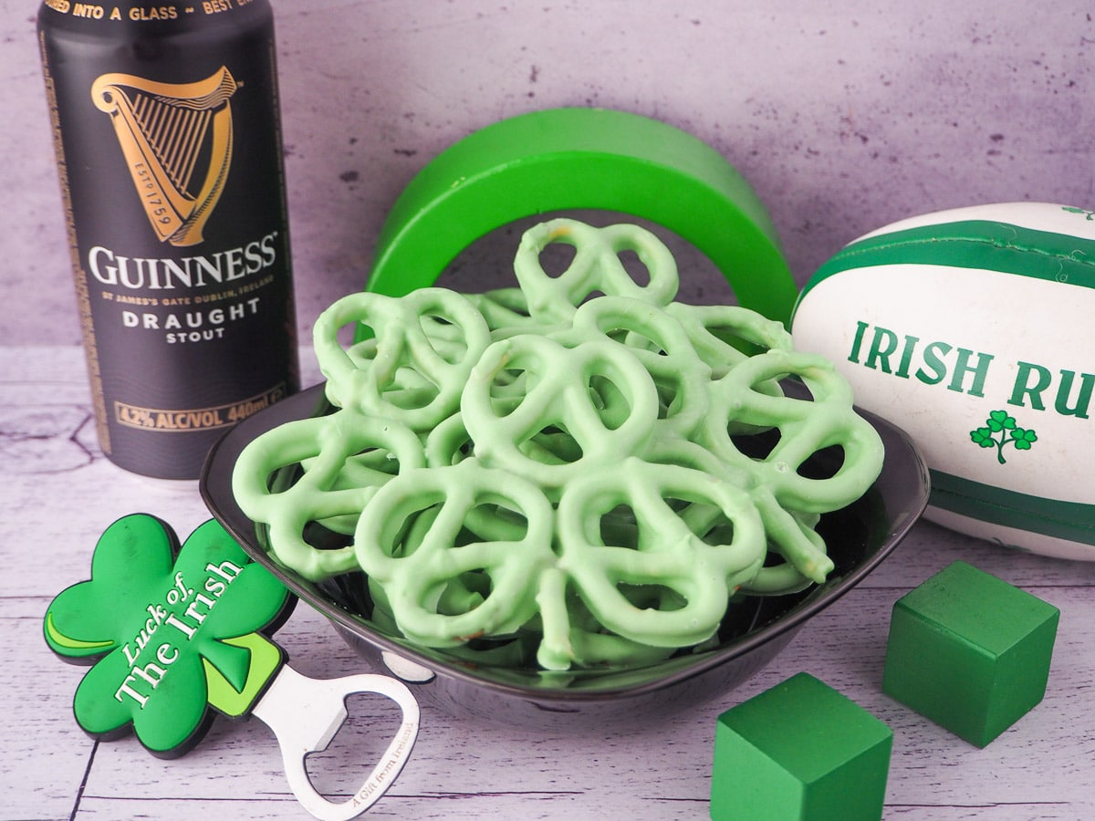 Shamrock pretzels in a black bowl to serve, surrounded by a Irish rugby call, can of Guinness, shamrock bottle opener and green blocks.