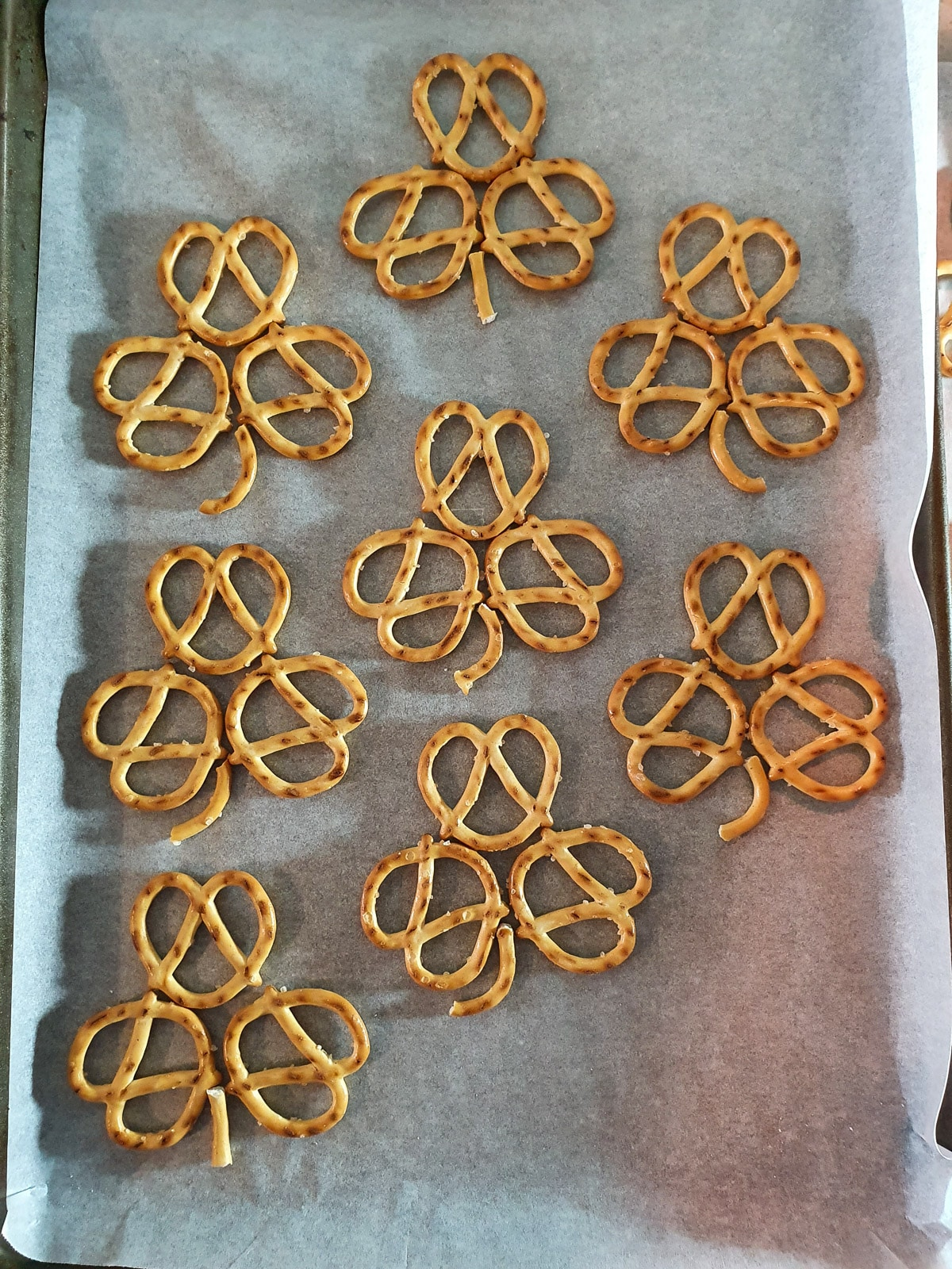 Uncoated pretzels laid out on baking tray ready to dip in chocolate