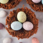 Close up top down view of shredded wheat nests, surrounded by extra speckled Easter eggs.