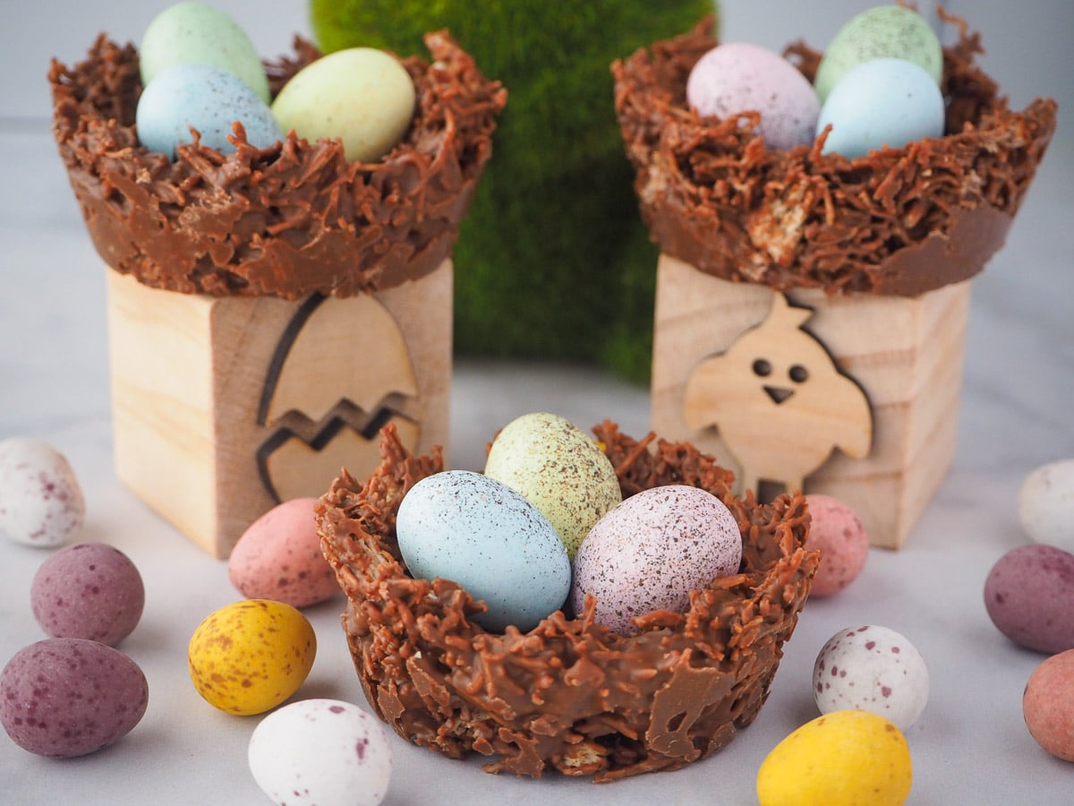 Group of three shredded wheat nests, surrounded by extra speckled Easter eggs, with two nests on Easter themed blocks and a green bunny figurine in the middle.