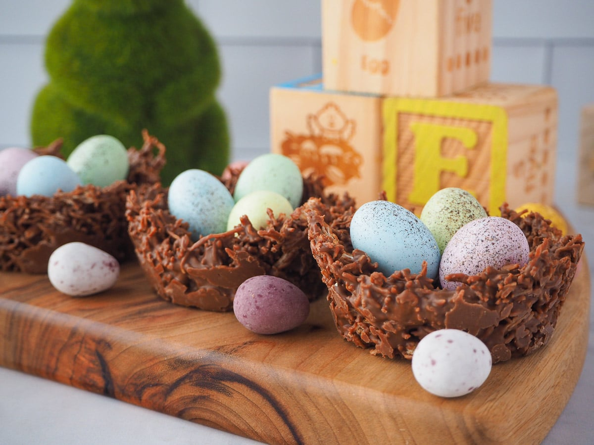 Row of three shredded wheat nests on a board, with extra speckled Easter eggs and Easter themed blocks and green bunny figurine in the background.