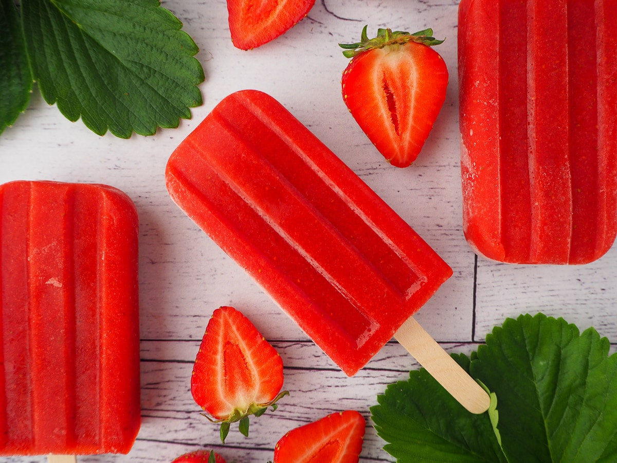 Row of three strawberry popsicles, surrounded by fresh strawberries and strawberry leaves.