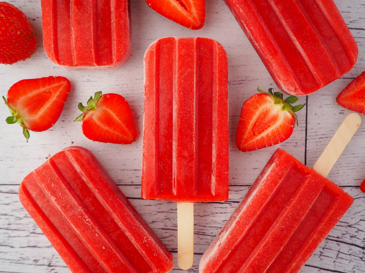 Close up of a strawberry popsicle, surrounded by fresh strawberries and other strawberry popsicles.
