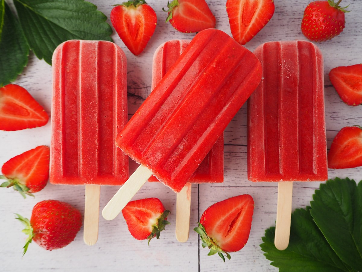 Row of three strawberry popsicles with a 4th stacked on top, surrounded by fresh strawberries and strawberry leaves.