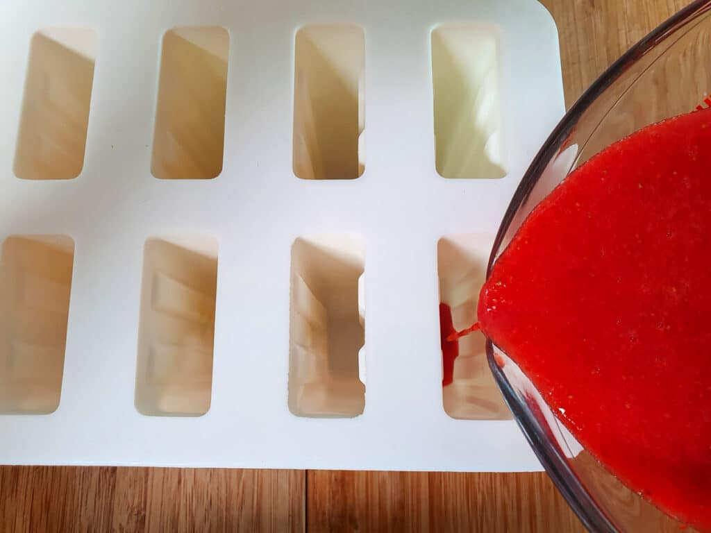 Filing popsicle molds with strawberry mix.
