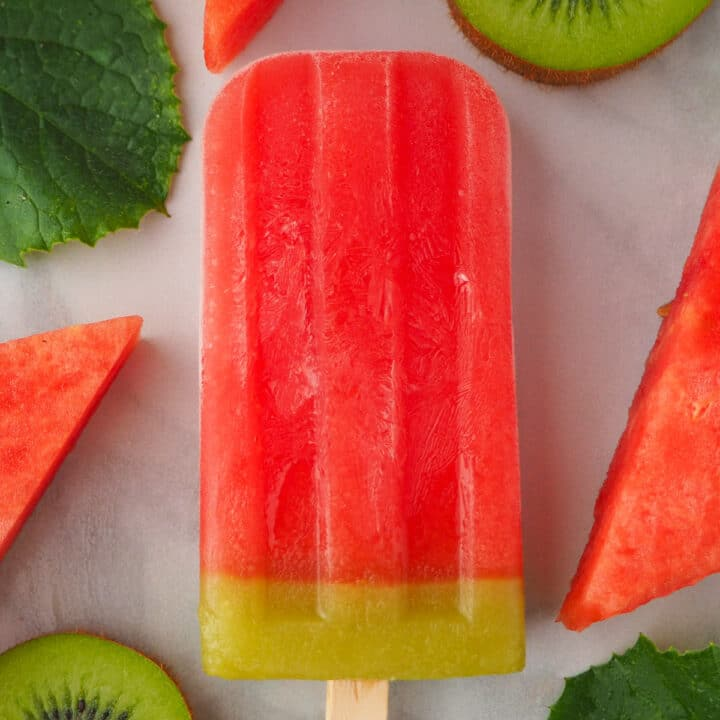 Single watermelon ice lolly surrounded by fresh watermelon, watermelon leaves and kiwi fruit.