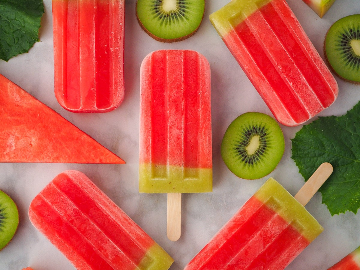Watermelon ice lollies surrounded by fresh watermelon, watermelon leaves and kiwi fruit.