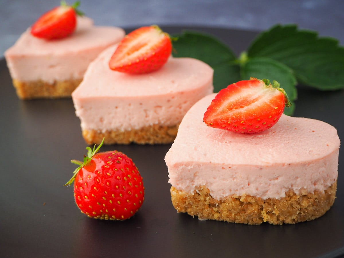 Side view three mini strawberry cheesecakes with fresh strawberries and strawberry leaves.