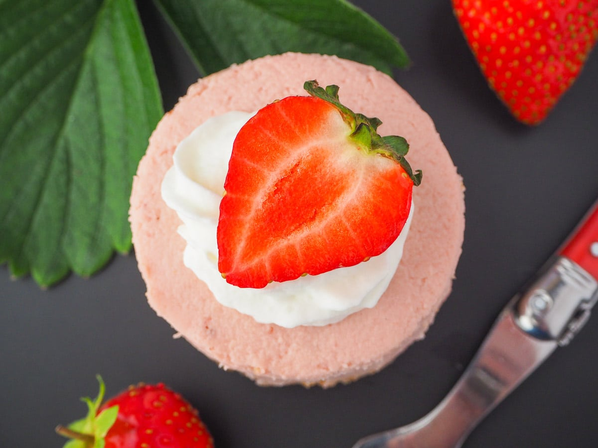 Round mini strawberry cheesecake with whipped cream, fresh strawberries, fresh strawberry leaves and a vintage fork.