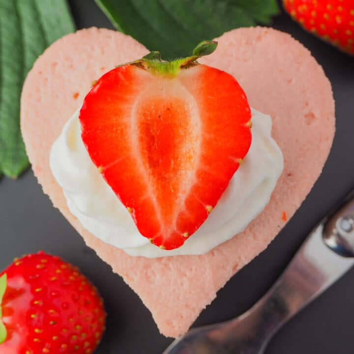 Close up heart shaped mini strawberry cheesecake with whipped cream, fresh strawberries, fresh strawberry leaves and a vintage fork.