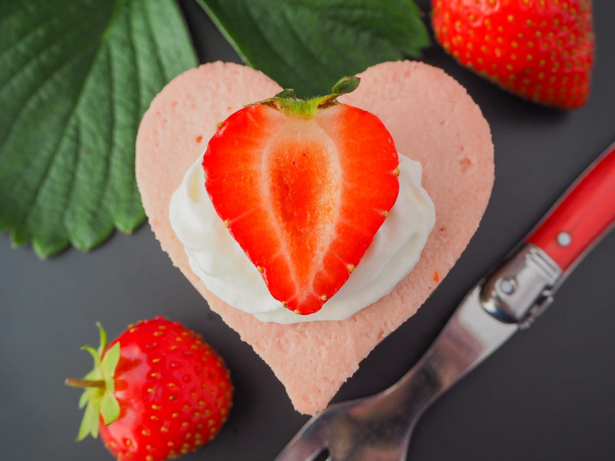 Heart shaped mini strawberry cheesecake with whipped cream, fresh strawberries, fresh strawberry leaves and a vintage fork.