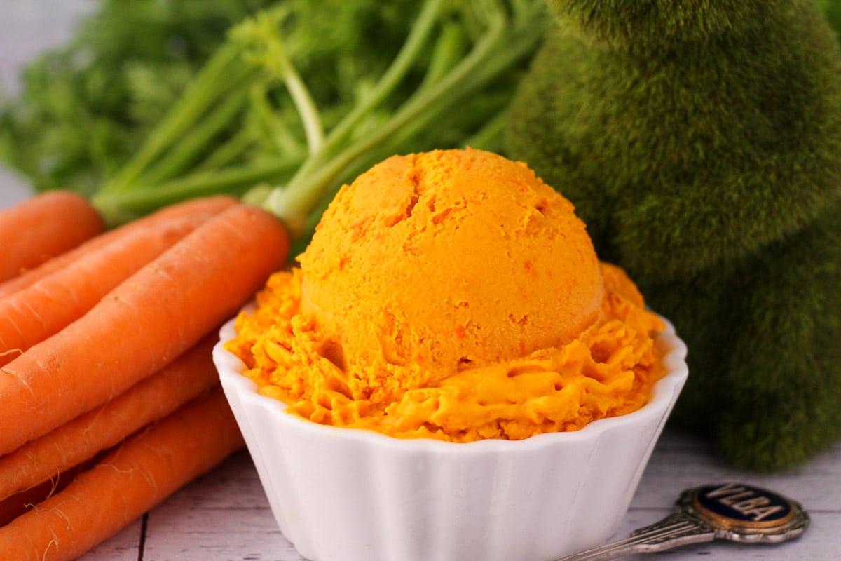 Scoop of carrot ice cream in a white bowl, with a vintage spoon and fresh Dutch carrots on the side, a green grass rabbit figure.