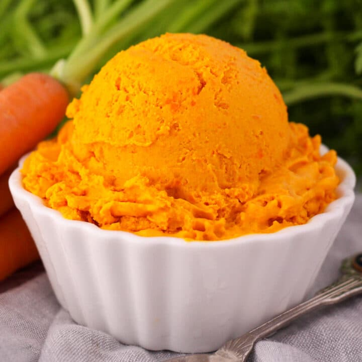 Close ups scoop of carrot ice cream in a white bowl, with a vintage spoon and fresh Dutch carrots on the side.