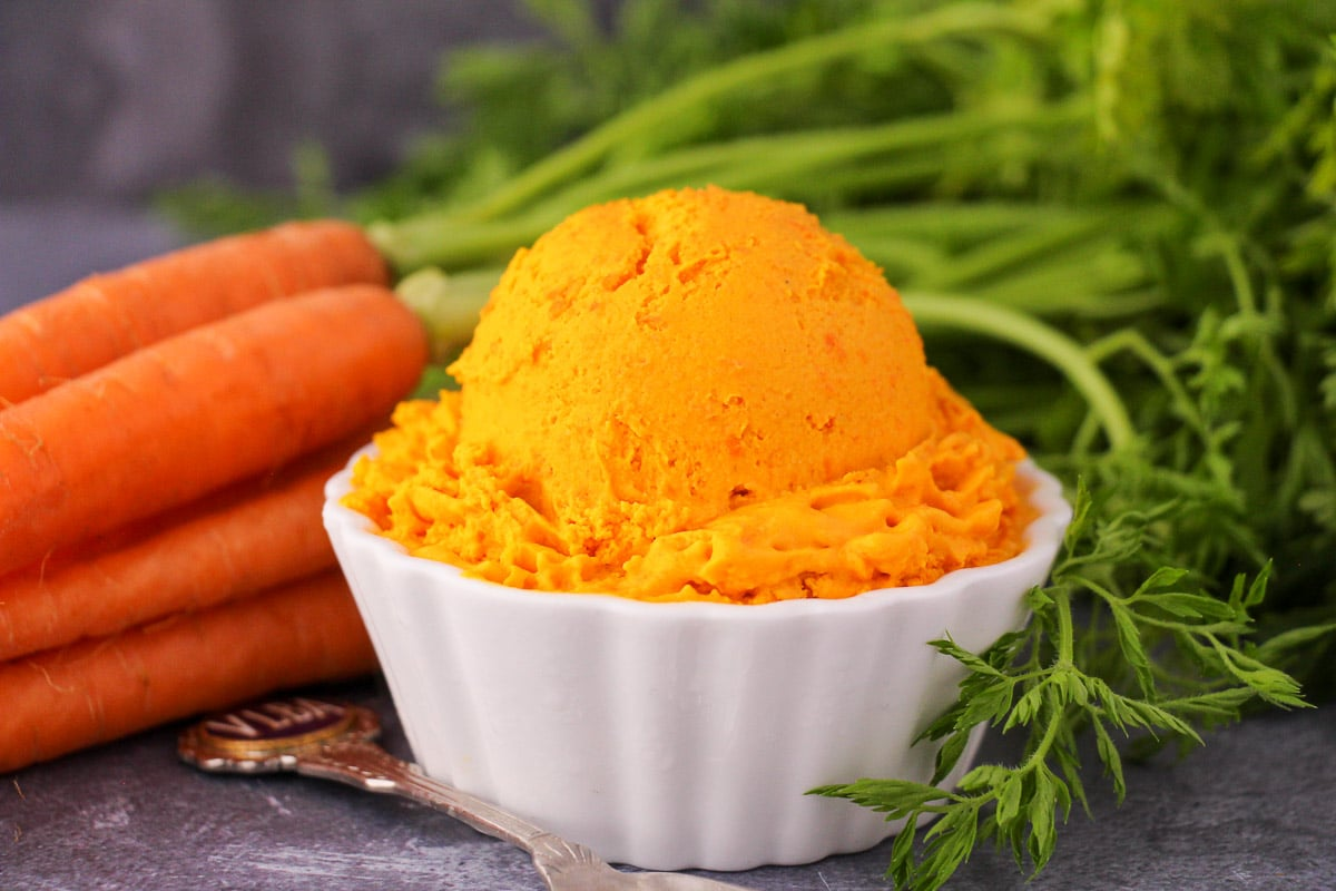 Scoop of carrot ice cream in a white bowl, with a vintage spoon and fresh Dutch carrots on the side.