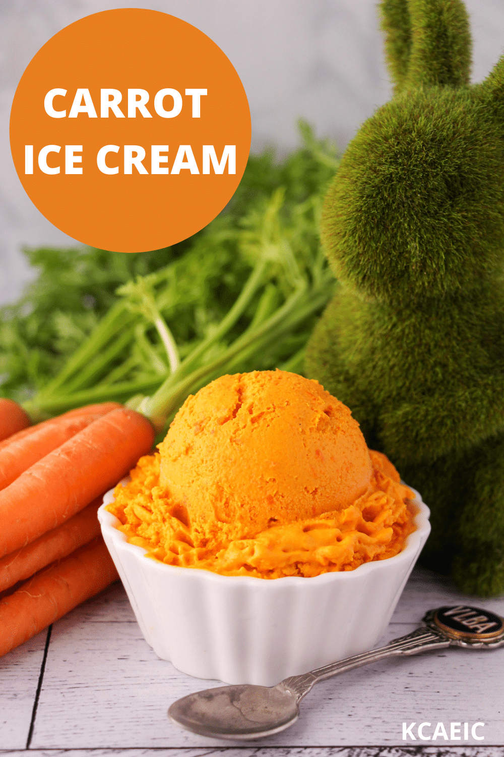 Scoop of carrot ice cream in a white bowl, with a vintage spoon and fresh Dutch carrots on the side, a green grass rabbit figure and text overlay, carrot ice cream, KCAEIC.